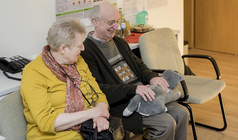 Älteres Ehepaar hat eine Stoffkatze auf dem Schoß und lacht.